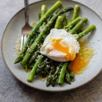 asparagus in bed with poached eggs and parmesan