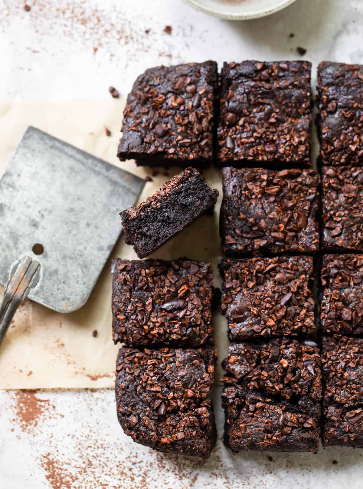 Olive Oil and Cocoa Brownies cut into squares, topped with cacao nibs