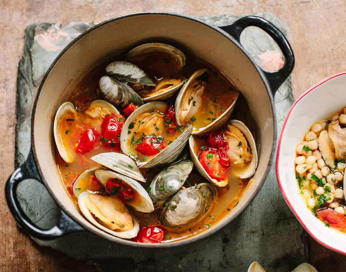 A black enamel Dutch oven filled with cooked clams and a broth with cherry tomatoes and chili with a serving bowl on the side.