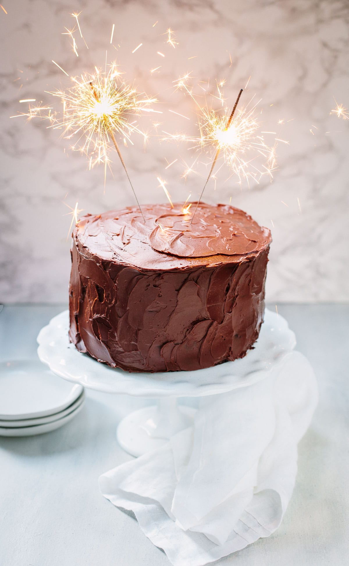 A frosted chocolate layer cake on a white cake stand with sparklers on top.