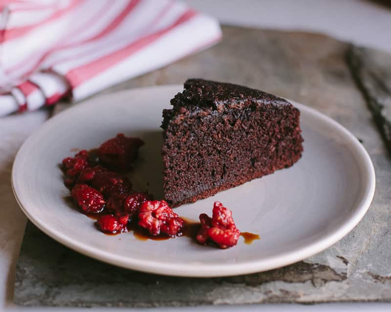 A slice of thick chocolate cake on a plate with vermouth soaked fresh raspberries.