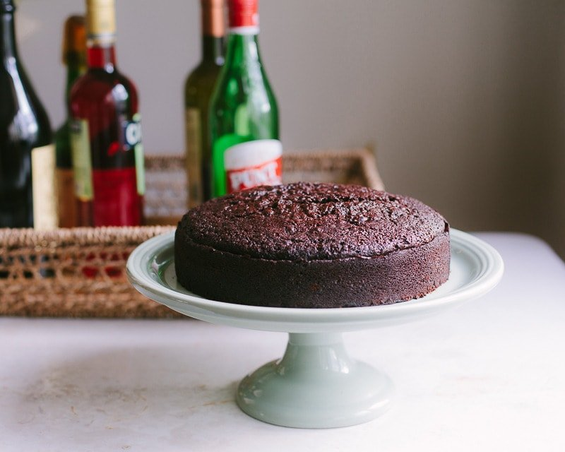 A chocolate cake on a cake stand with bottles of liqueur in the background.