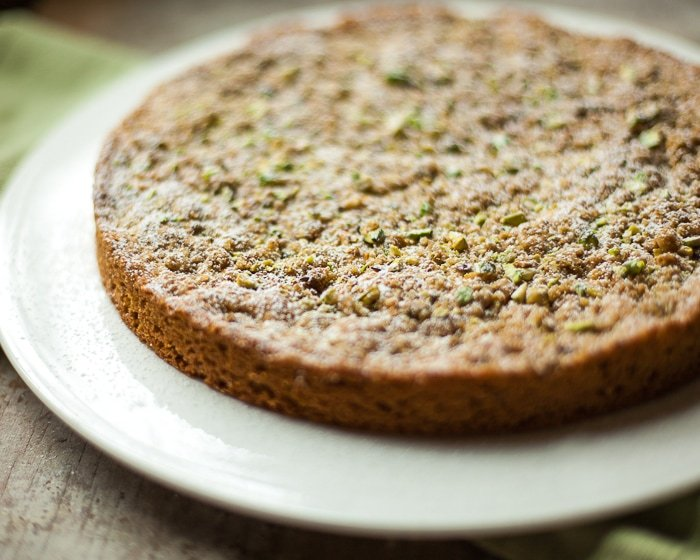 A round coffee cake topped with pistachio crumble and powdered sugar on a plate.