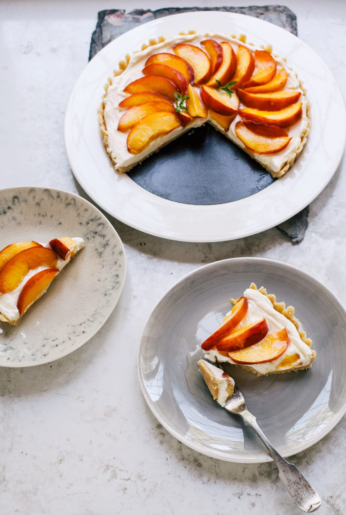 A cream cheese tart topped with wedges of fresh peaches on plates.