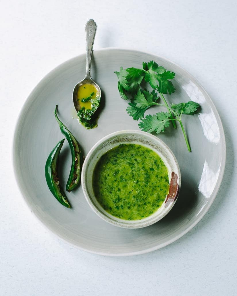 A gray bowl filled with pureed salsa verde, an herb sauce with jalapeno pepper, olive oil and cilantro leaves.