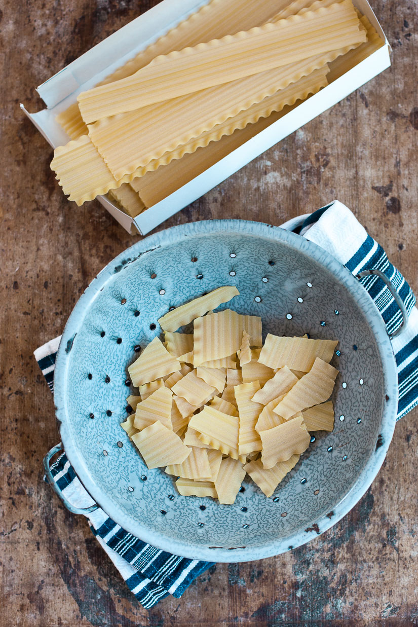 Lasagna noodles broken into pieces in a blue metal colander.