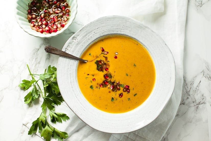 A bowl of creamy sweet potato soup with fresh pomegranate salsa on top