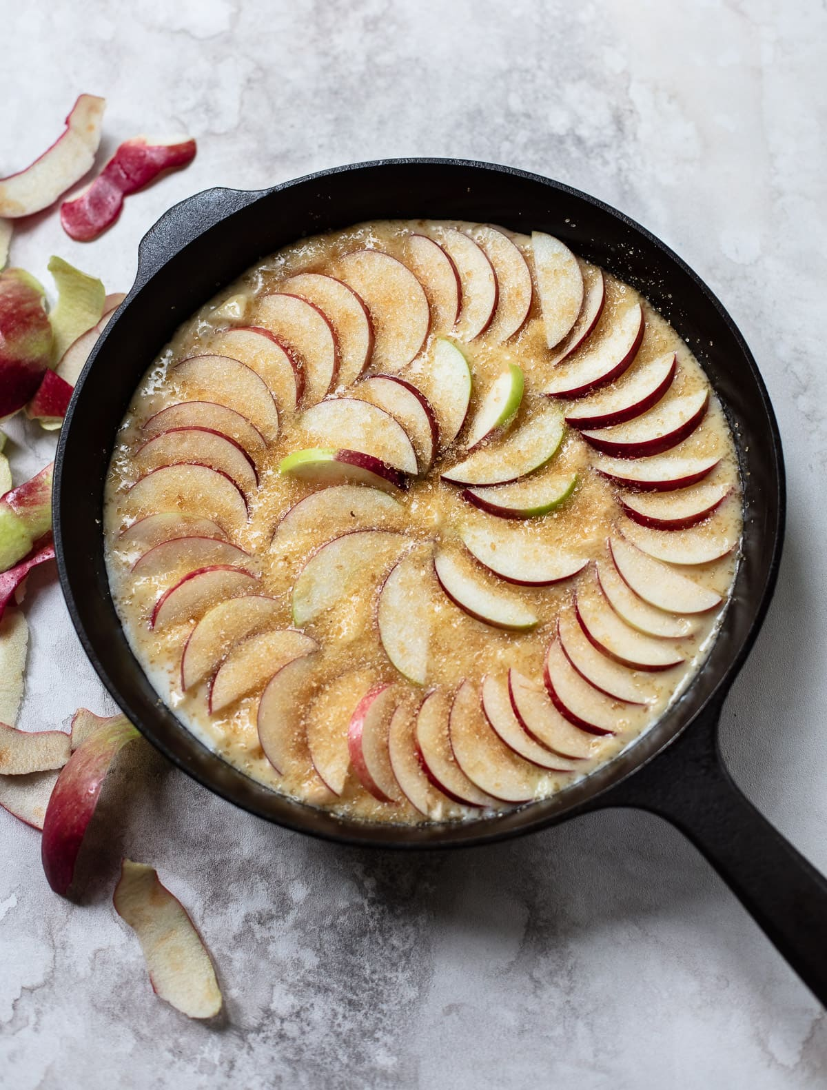 A black cast iron skillet with whiskey-infused cake, sliced apples and powdered sugar on top.