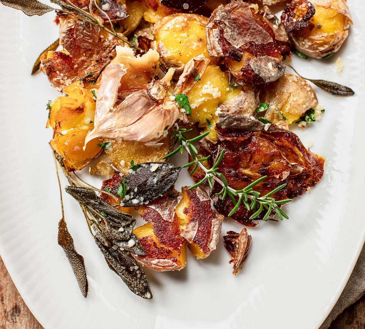 Image of an oval white platter with crispy roasted yellow potatoes with sage and rosemary sprigs on a wood background on top of a linen napkin
