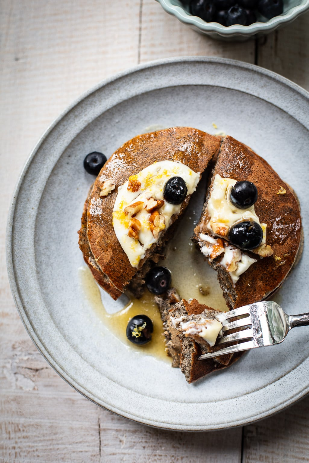 A stack of buckwheat flour pancakes on a gray plate, topped with blueberries, maple syrup and butter.