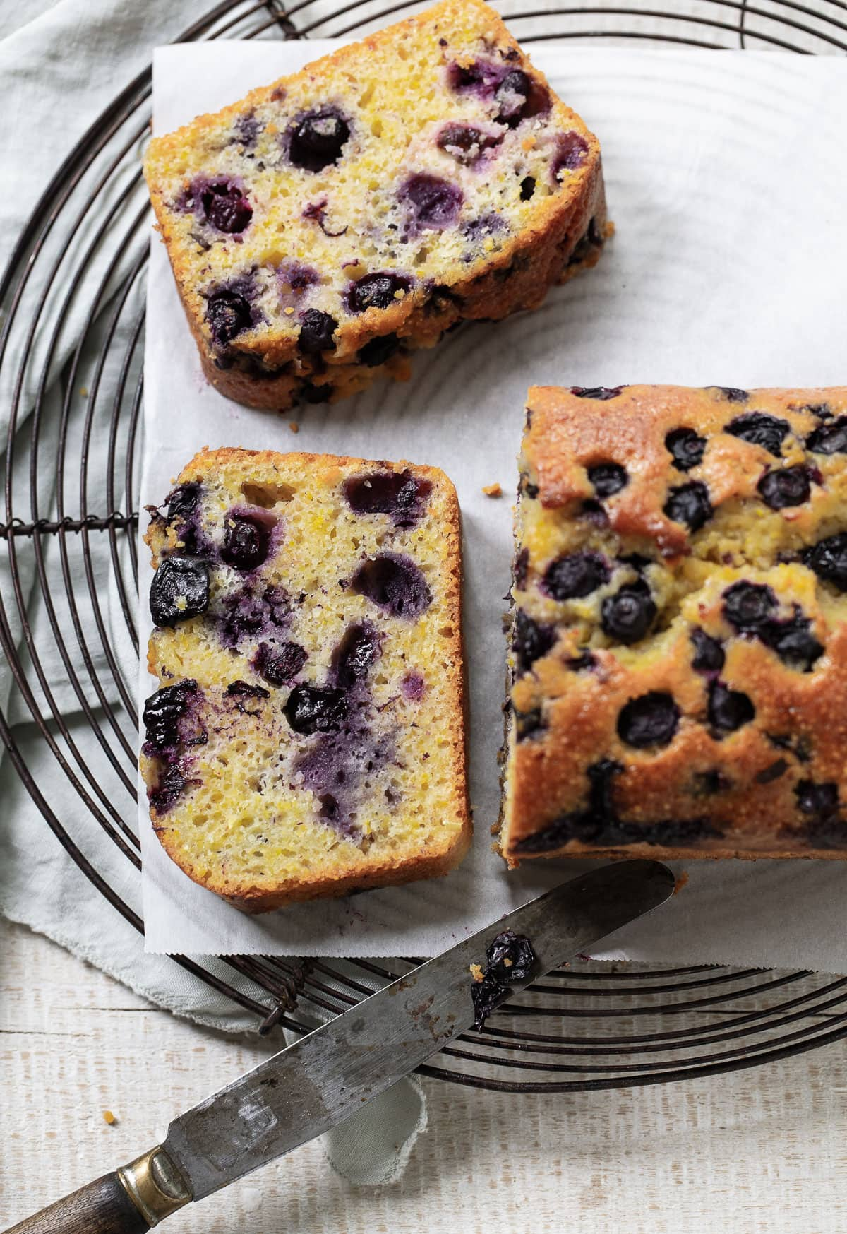 Blueberry loaf cake sliced into thick pieces on a cooling rack