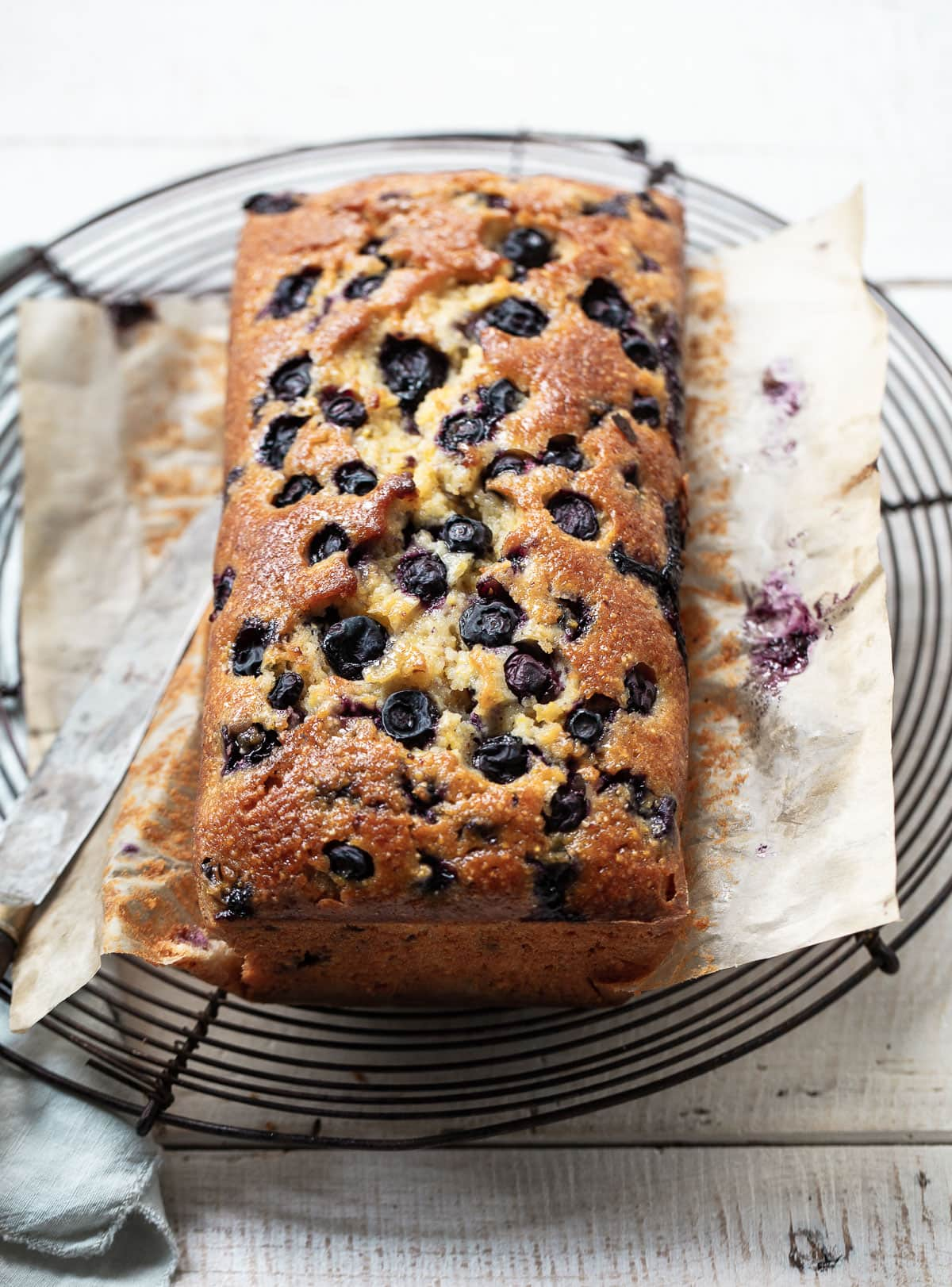 Baked and sliced cornmeal loaf cake with jammy blueberries on a cooling rack