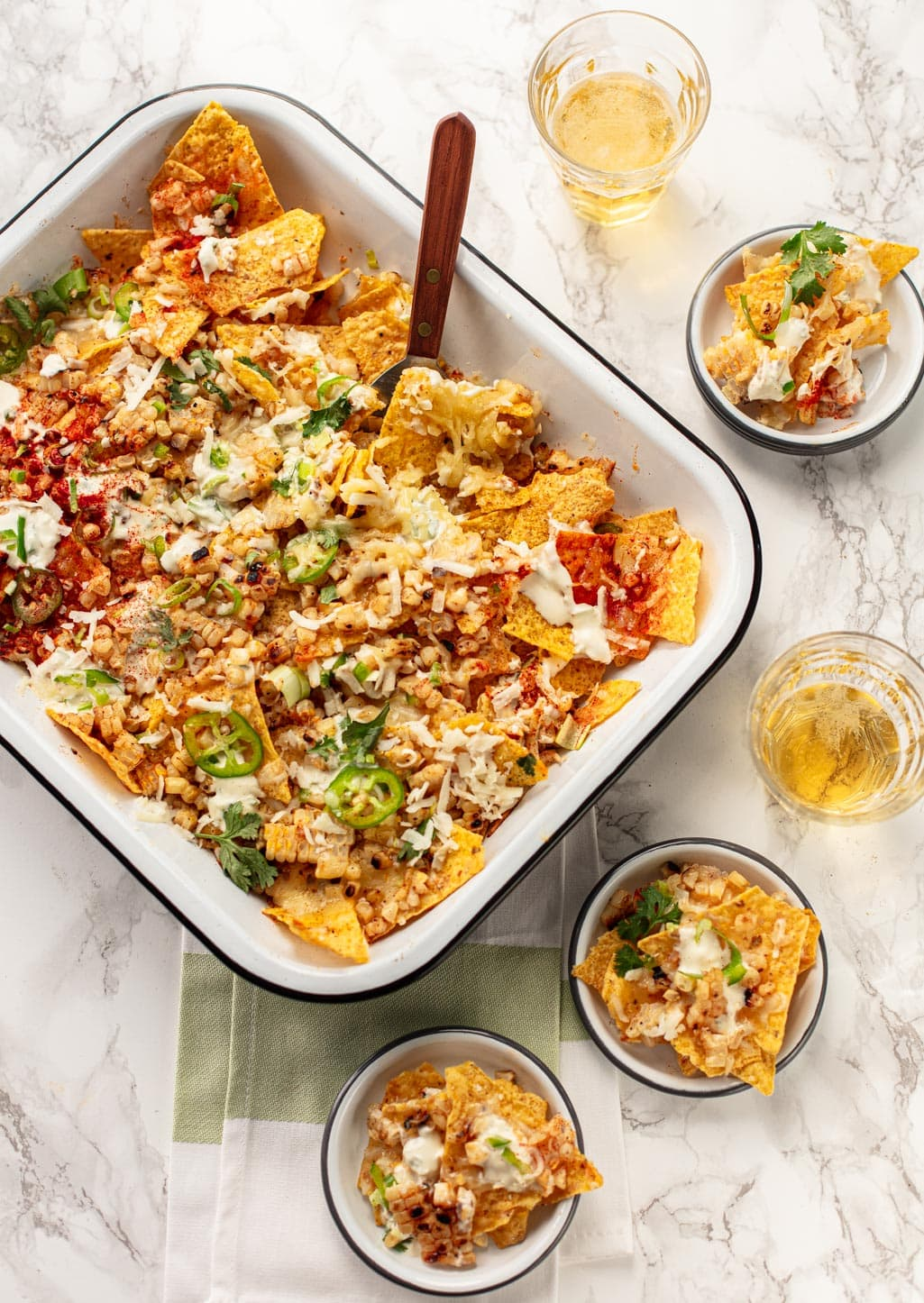 Mexican Corn Nachos with cheese and crema with glasses of beer on the side.