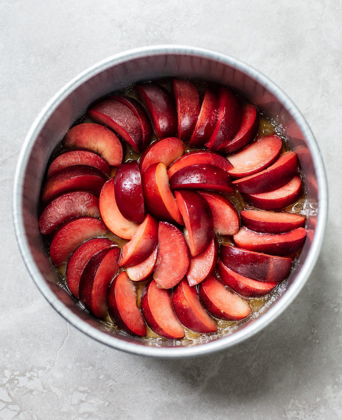 sliced plums with melted sugar arranged concentrically in a cake pan
