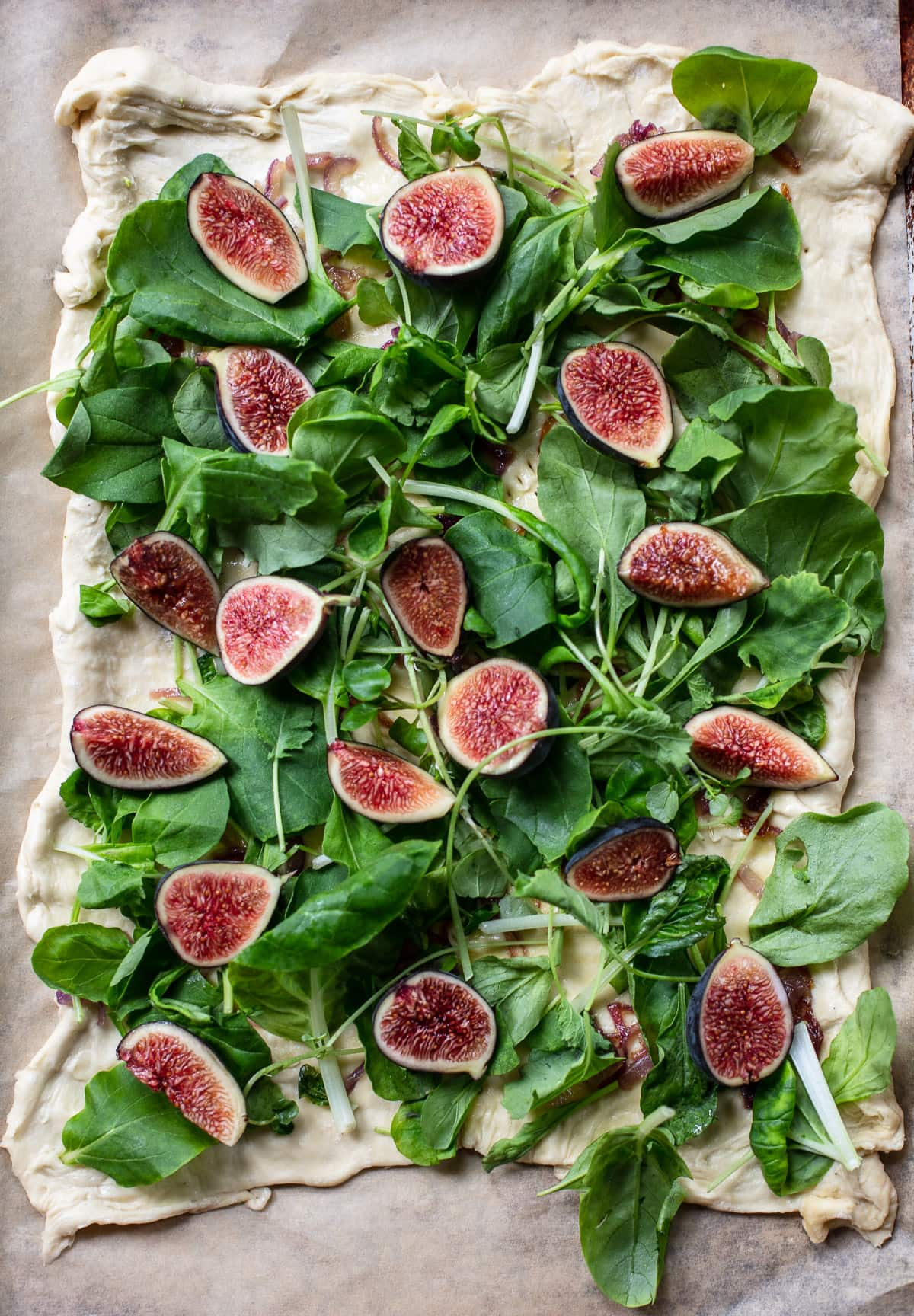 Puff pastry appetizer on a piece of parchment paper, topped with wedges of fresh figs, blue cheese and arugula greens.