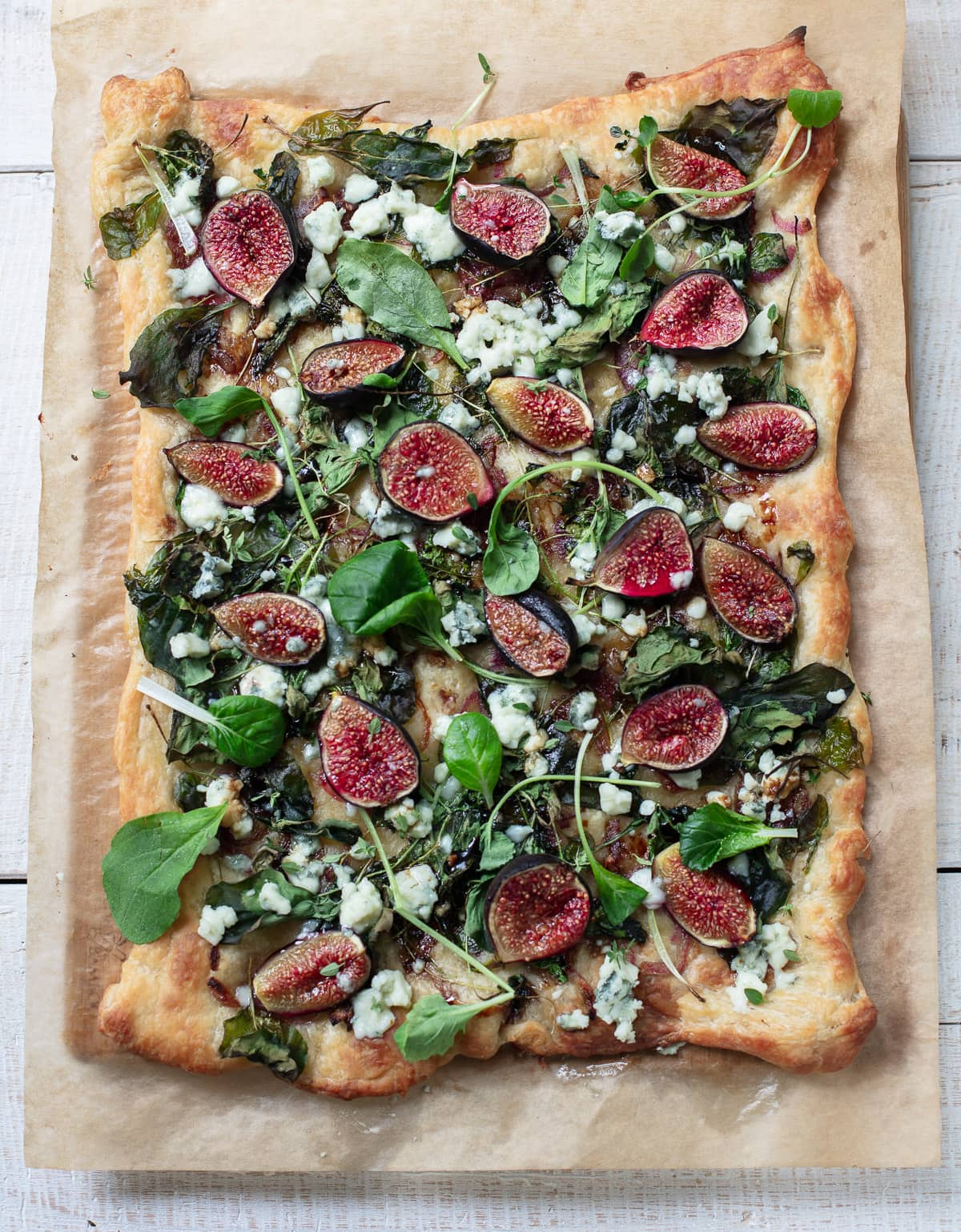 Slices of puff pastry appetizer topped with wedges of fresh figs, blue cheese and arugula greens.