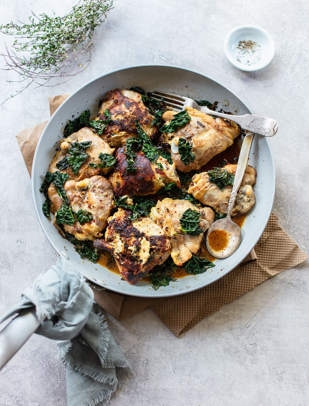 Skillet Herb Dijon Chicken in a gray pan with a fringed towel pot holder