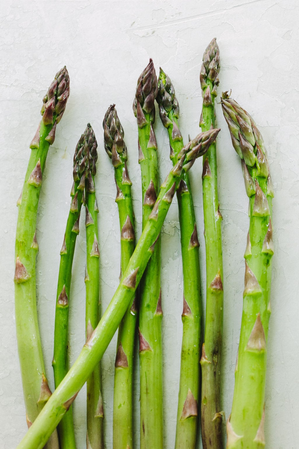 Raw green asparagus spears on a grey background.