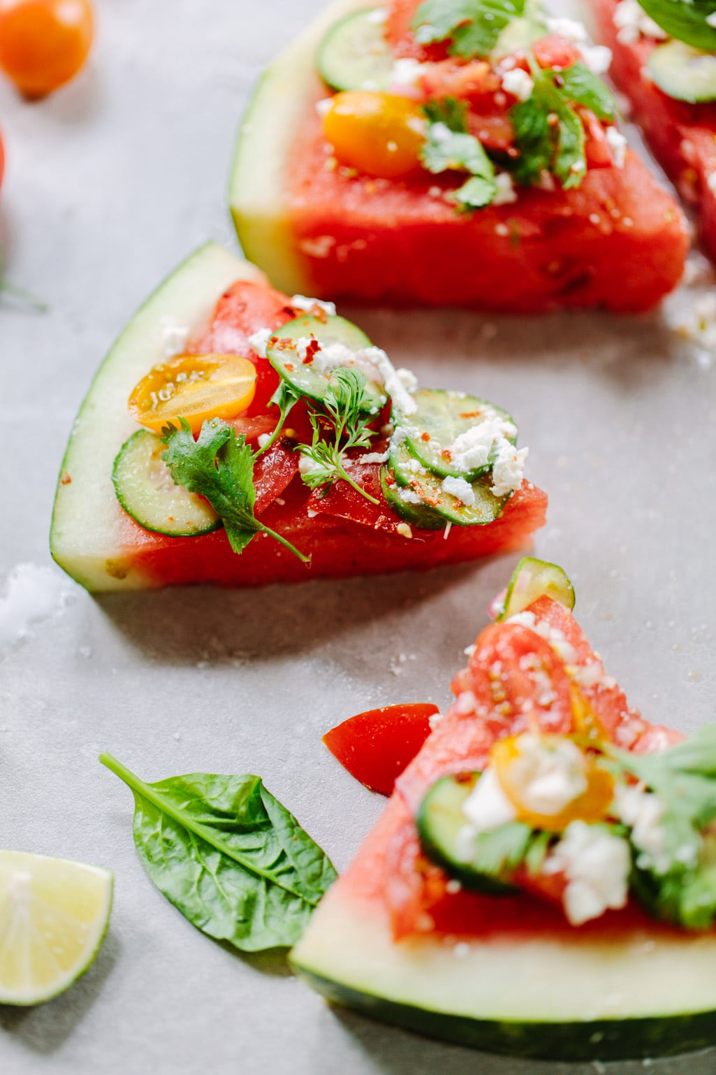 Watermelon wedges topped with a Mediterranean salad of cucumber, feta and tomatoes.