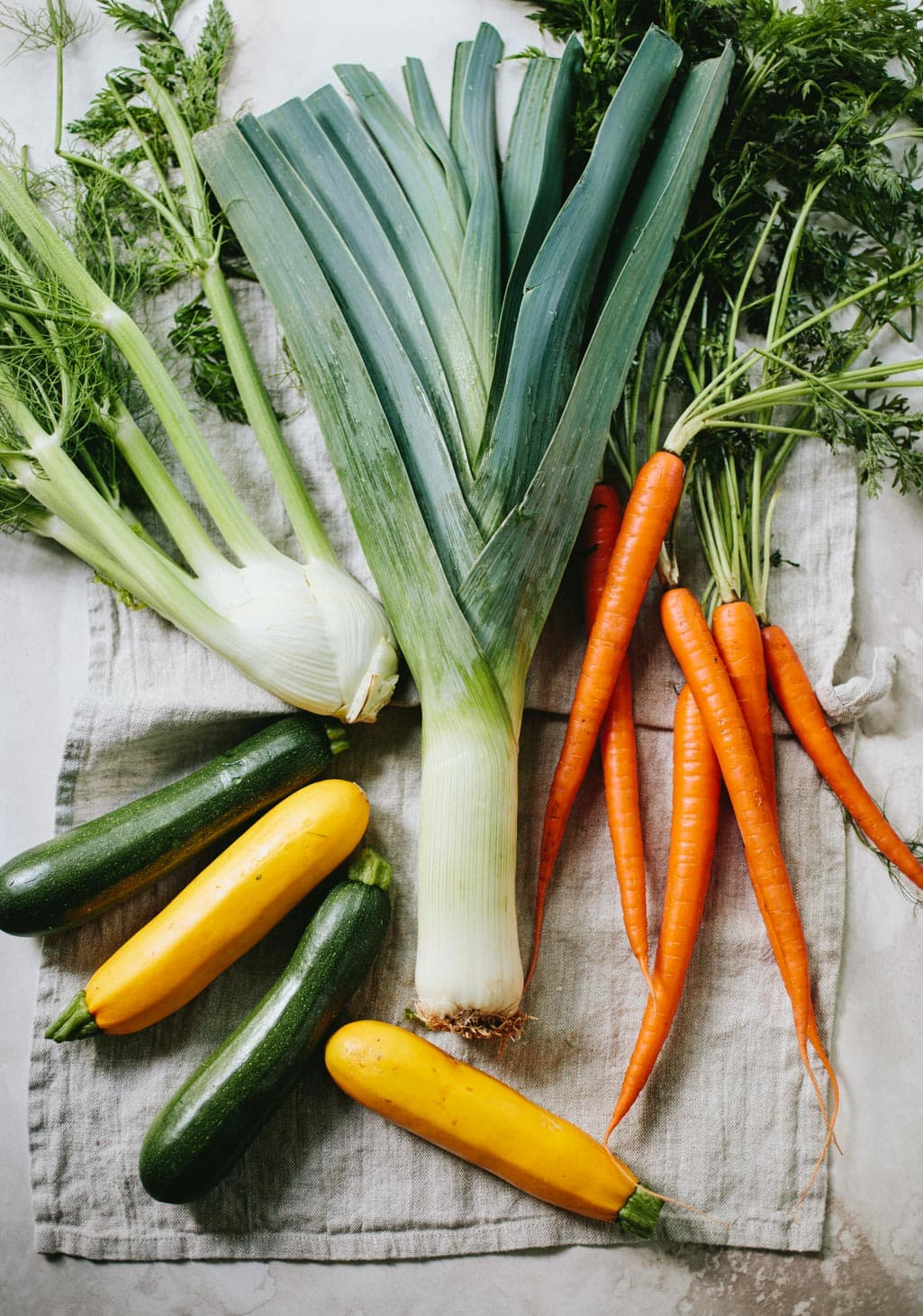 Fresh summer produce on a linen napkin, showing a bunch of leeks, carrots, fennel bulb and green and yellow summer squash.