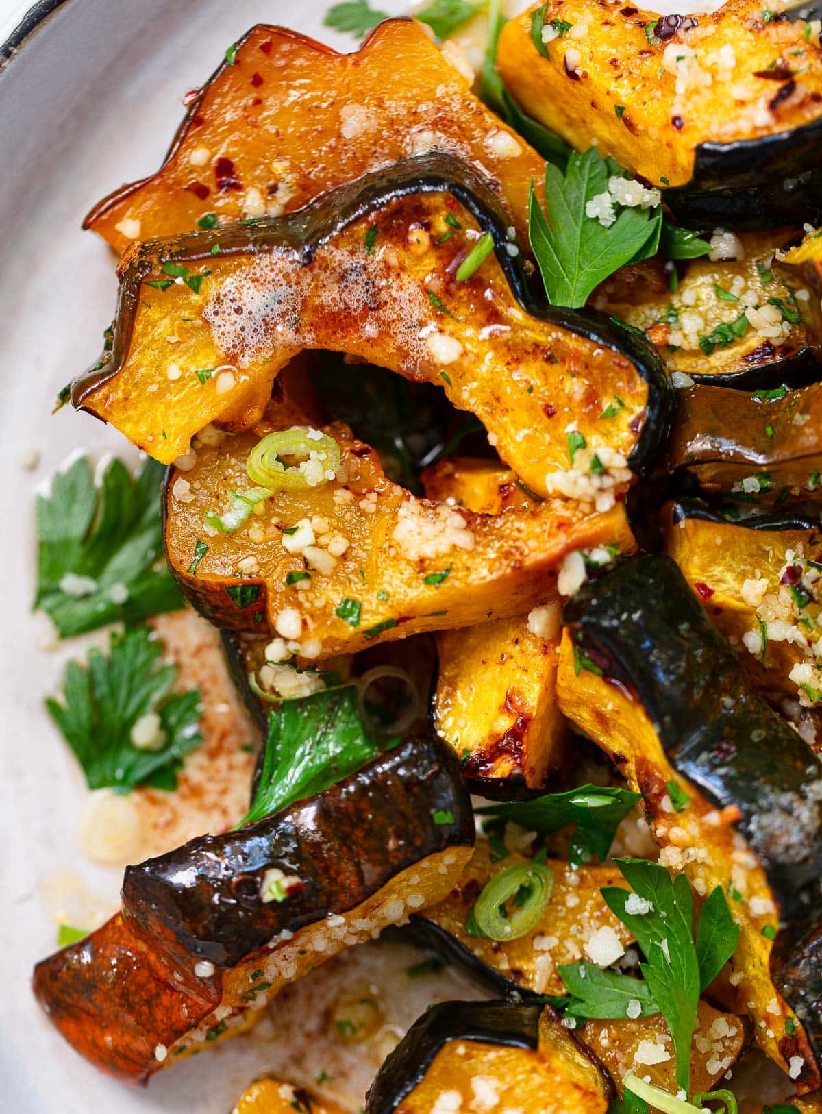 Roasted Acorn Squash with Brown Butter on a plate with parsley, green onion and cheese on top