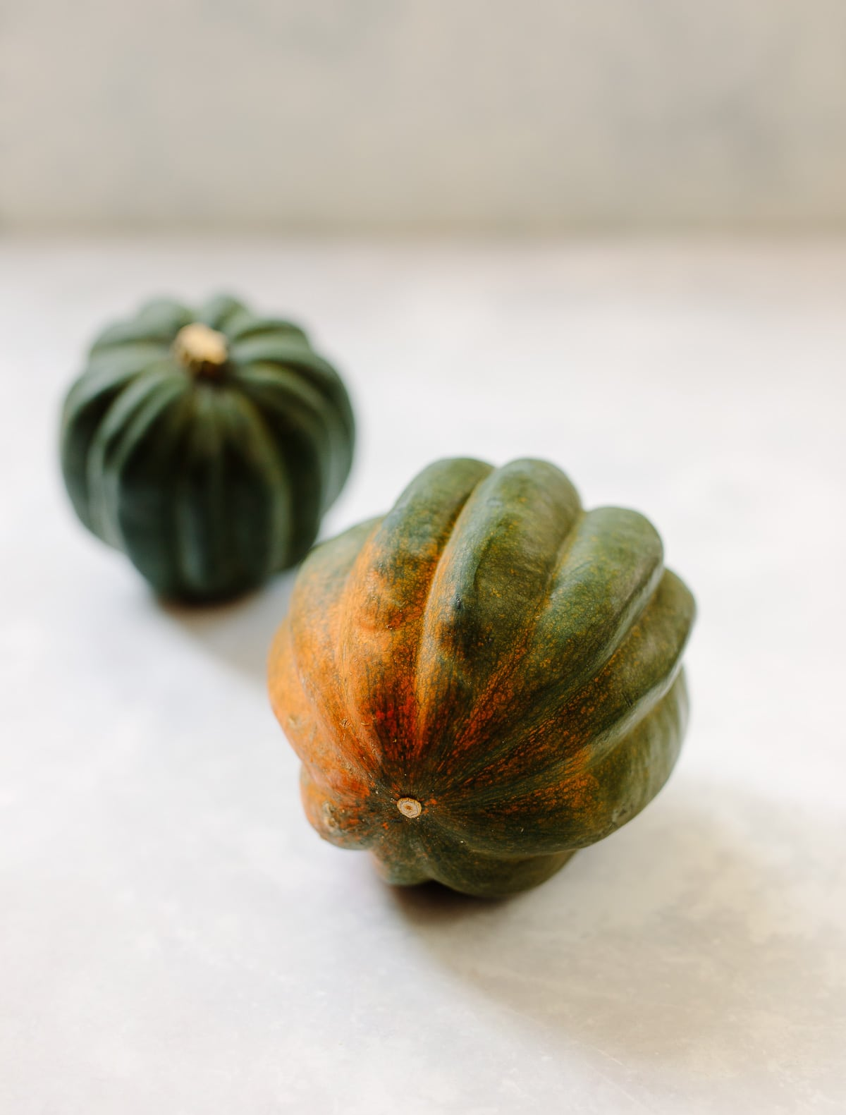 Image of two acorn squash on a white marble counter