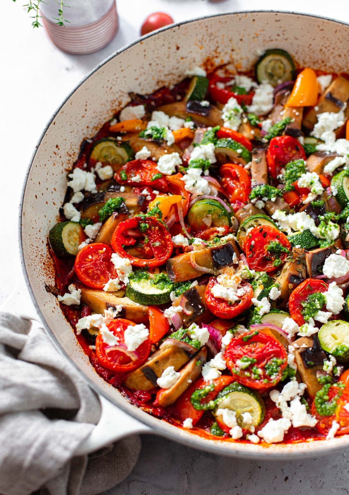 A round white casserole dish with bake Mediterranean vegetables for ratatouille, topped with crumbed goat cheese.