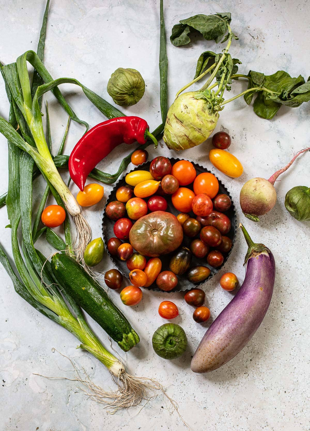 Summer vegetables: Multi-colored tomatoes, zucchini, peppers, onions, greens
