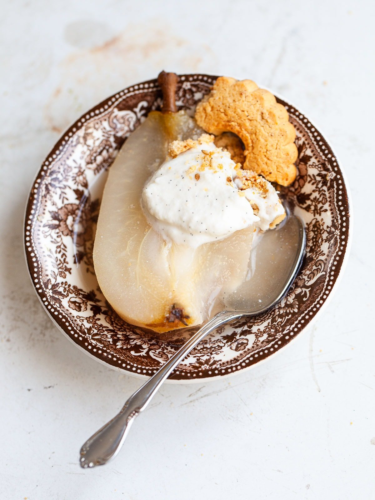 A brown transferware dish with a poached pear and spoon, topped with ricotta cream and a crumbled cookie.