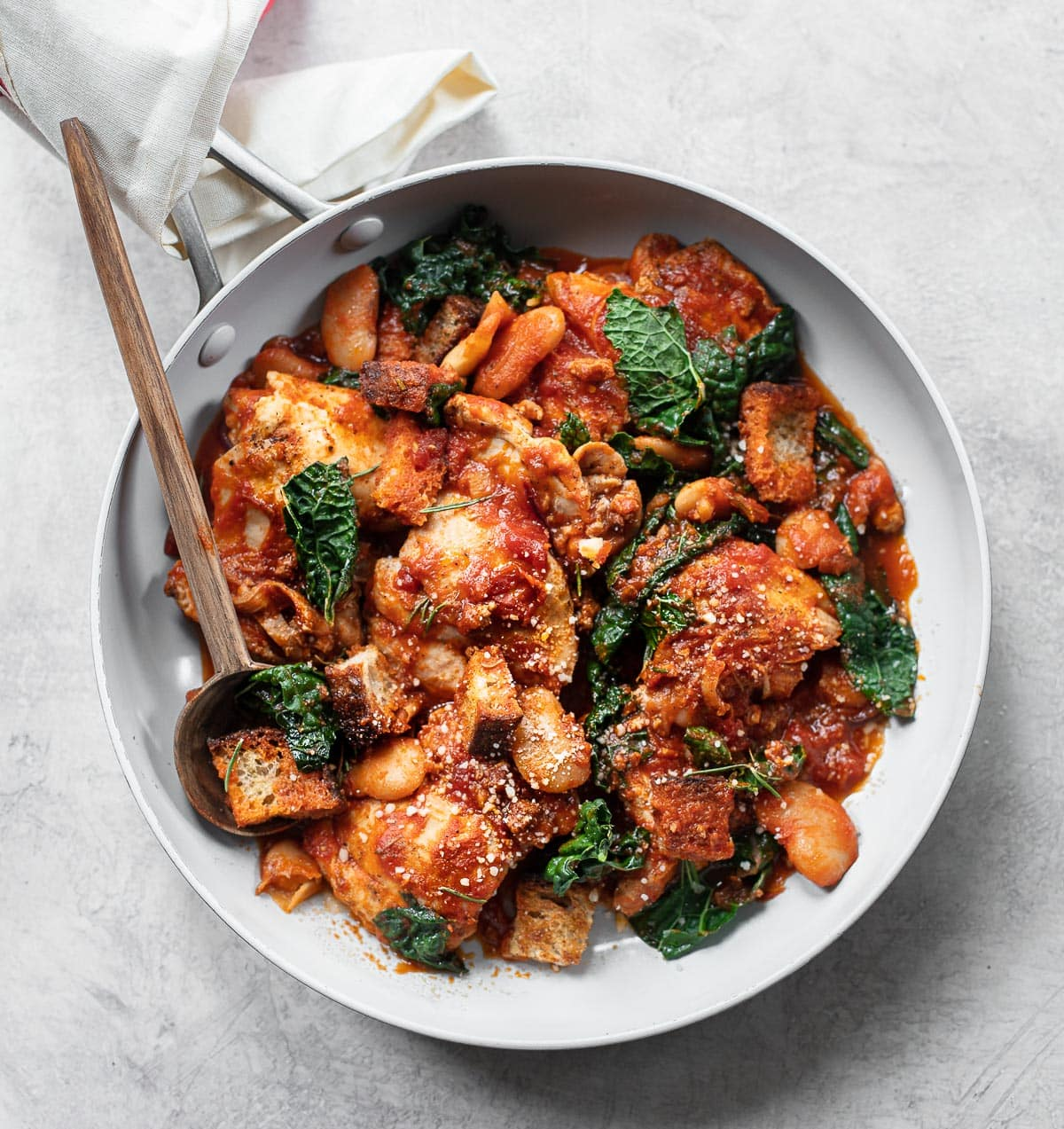 A skillet recipe for boneless chicken thighs in tomato sauce with kale, white beans and sourdough bread.