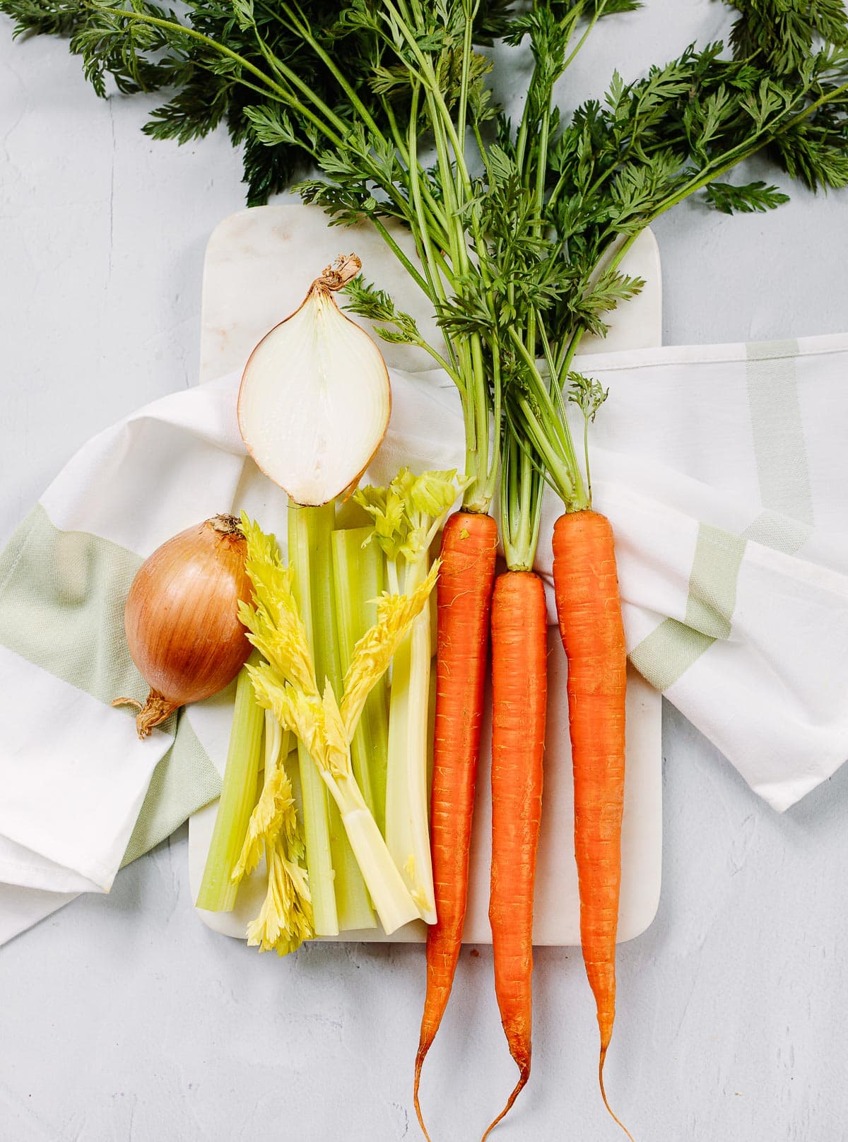 Fresh produce ingredients for homemade chicken soup: onion, celery and carrots.
