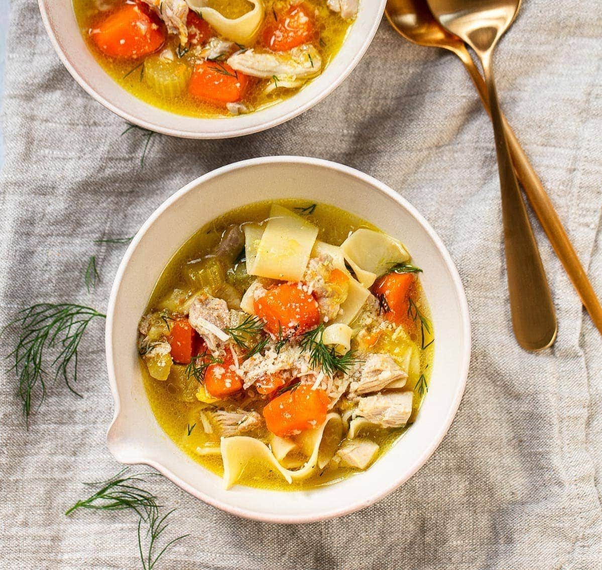 Simple white bowl of chicken noodle soup, with fresh dill.