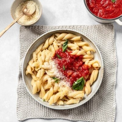 A bowl of curly pasta topped with pomodoro sauce, a recipe that includes canned tomatoes, basil and Parmesan cheese.
