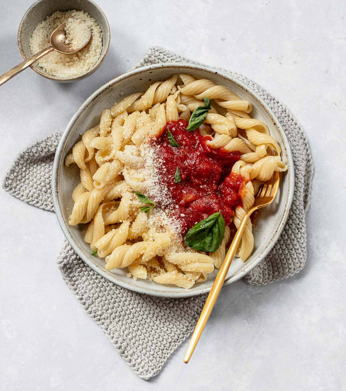A bowl of pasta and pomodoro sauce with a fork on top of a knitted towel and cheese on the side.