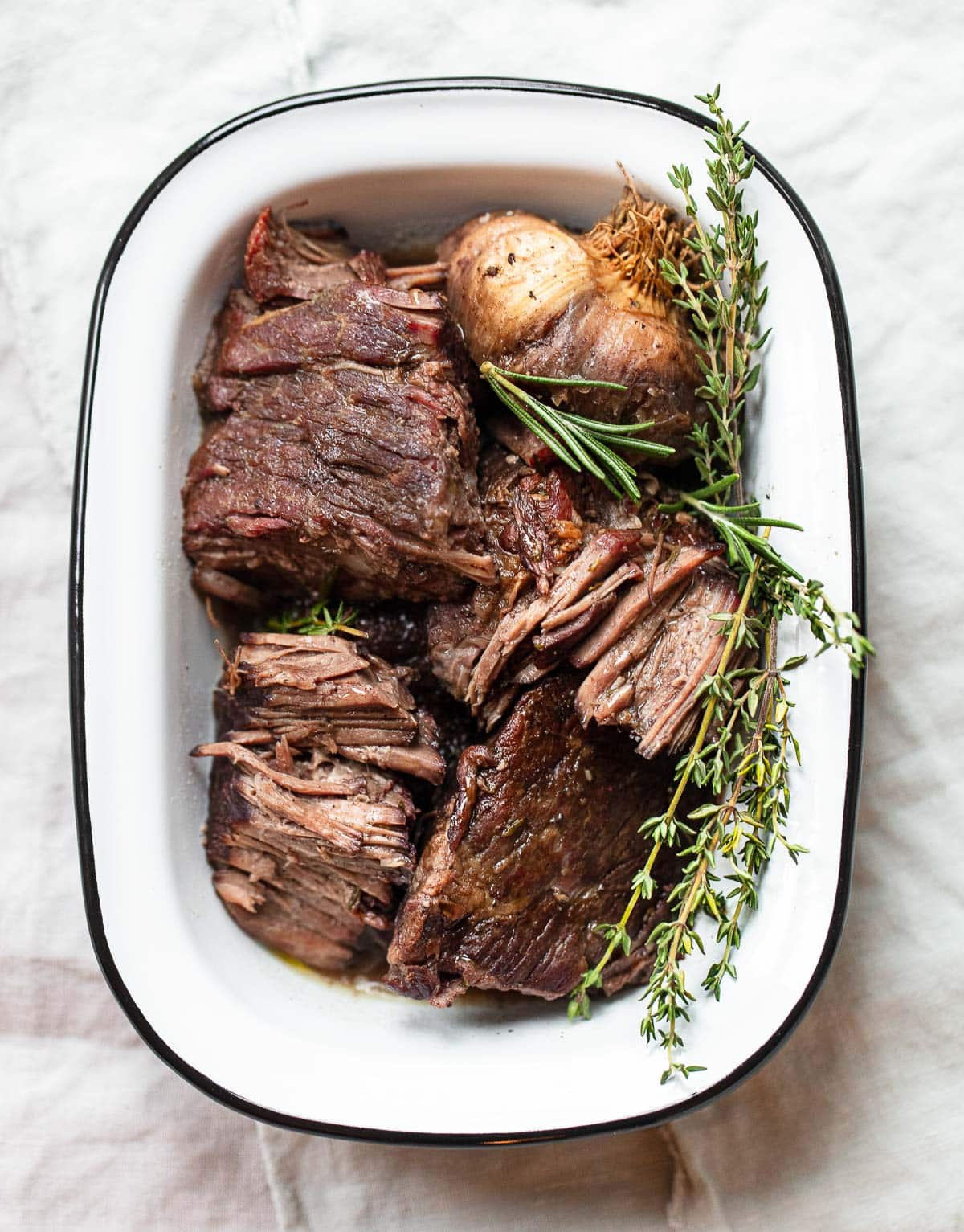 Chunks of braised beef short ribs in a white enamel baking pan, garnished with garlic, fresh thyme and rosemary sprigs.