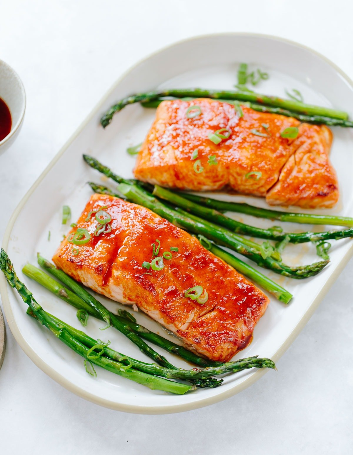 Two glazed salmon fillets on a platter, with grilled asparagus and sliced scallion greens.