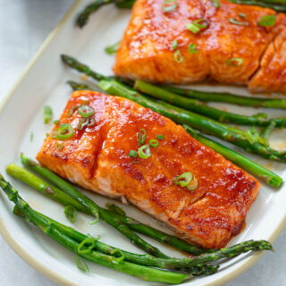 Glazed salmon on a white platter with asparagus spears and chopped green onion.