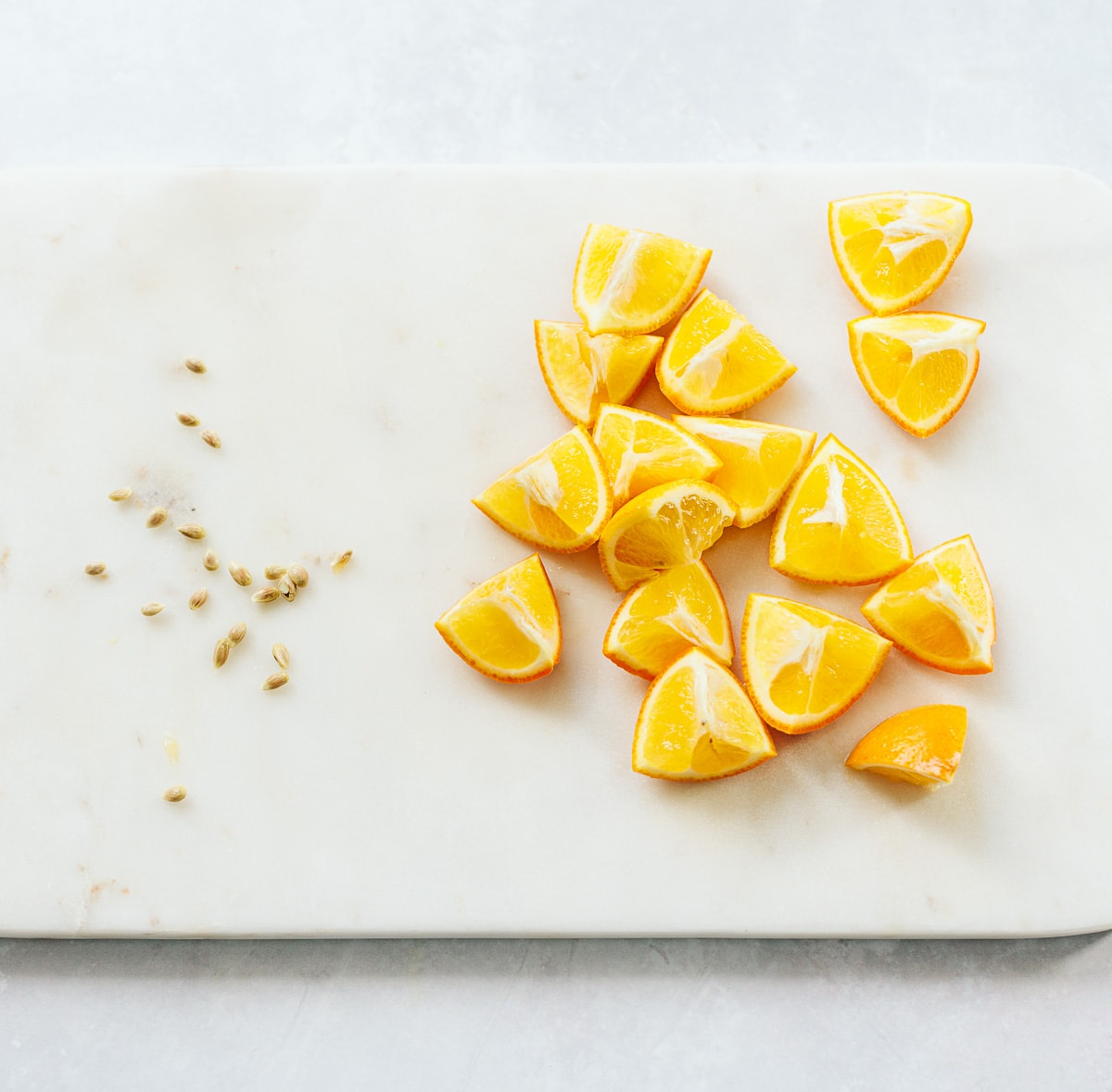 Wedges of Meyer lemon on a marble board, with seeds removed.