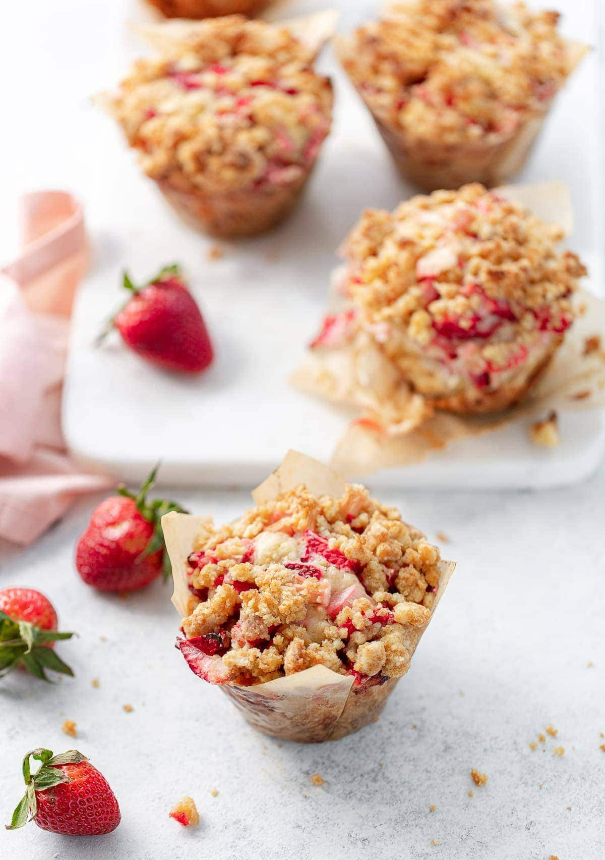 Oversized strawberry rhubarb muffins in bakery parchment paper.