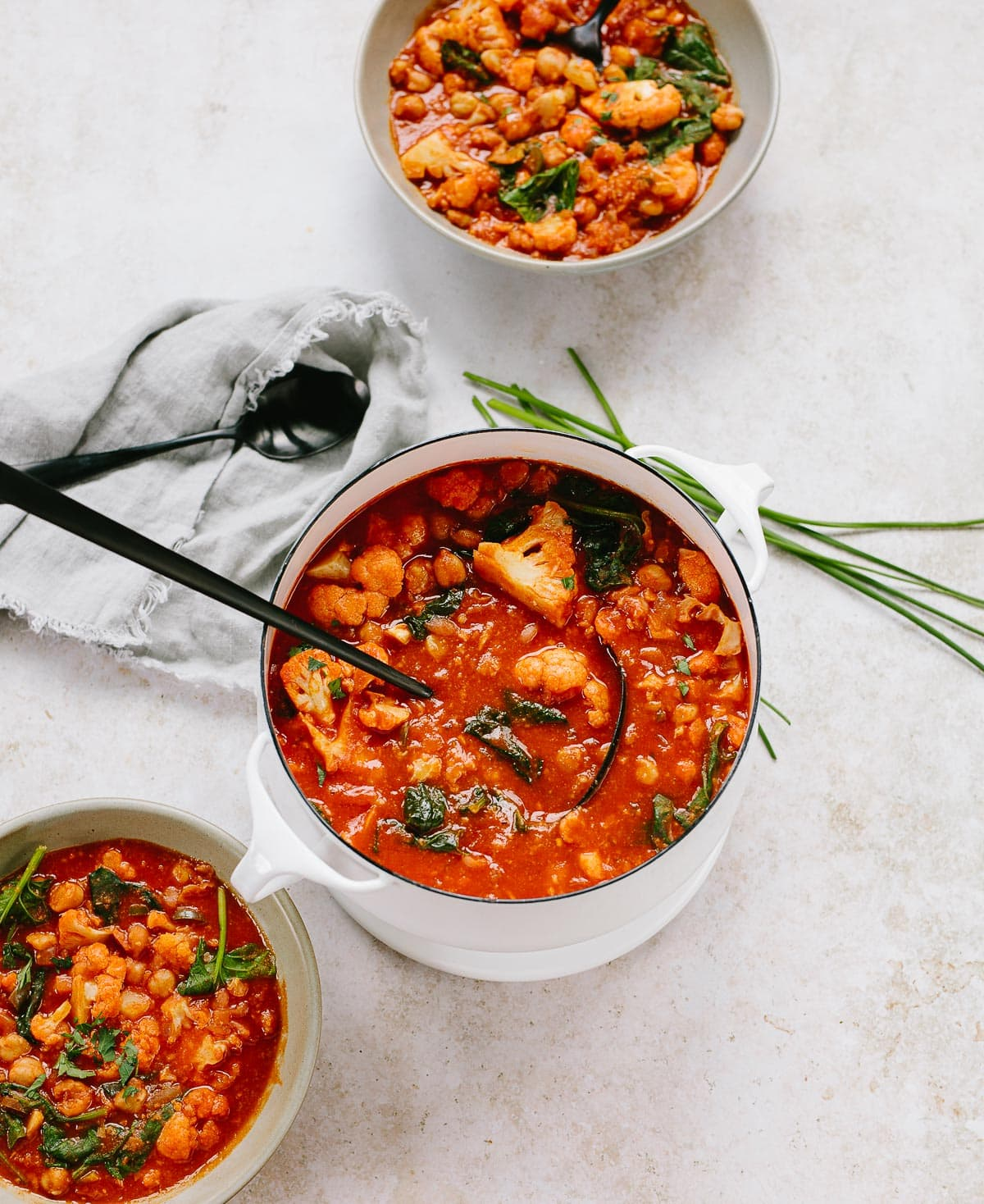 A vibrant red tomato-based chickpea and cauliflower stew in a white soup pot and ladle, served into bowls.