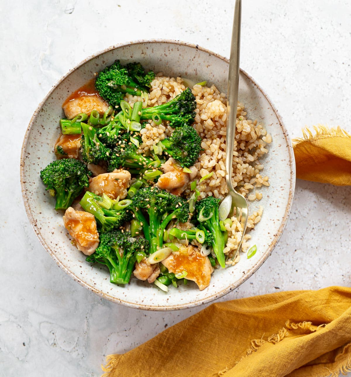 A gray ceramic bowl full of short grain brown rice, chunks of chicken and broccoli florets in a sesame glaze.