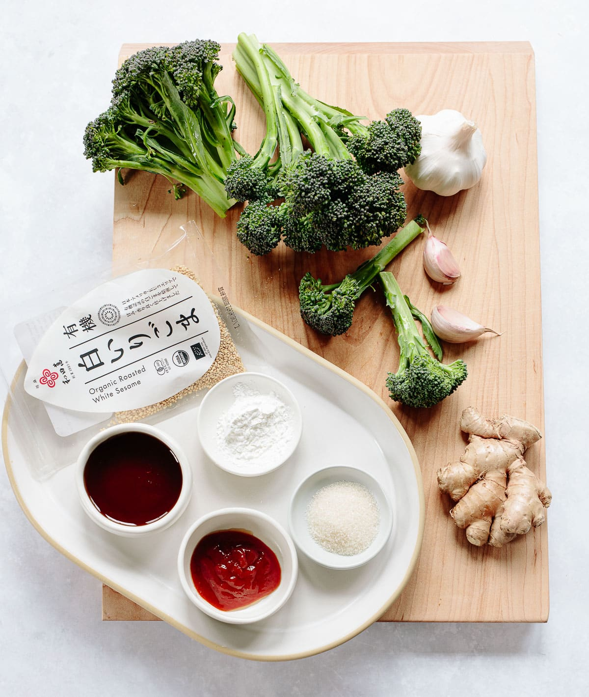 Ingredients for Chinese-style chicken and broccoli on a plate and maple cutting board: Fresh broccoli, garlic, ginger, sesame, sugar, soy sauce and cornstarch.