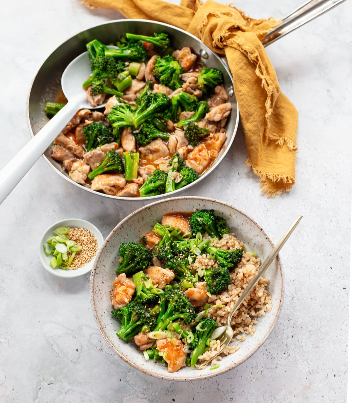 Chicken and broccoli stir-fry in a skillet with a serving spoon and a bowl serving with rice.