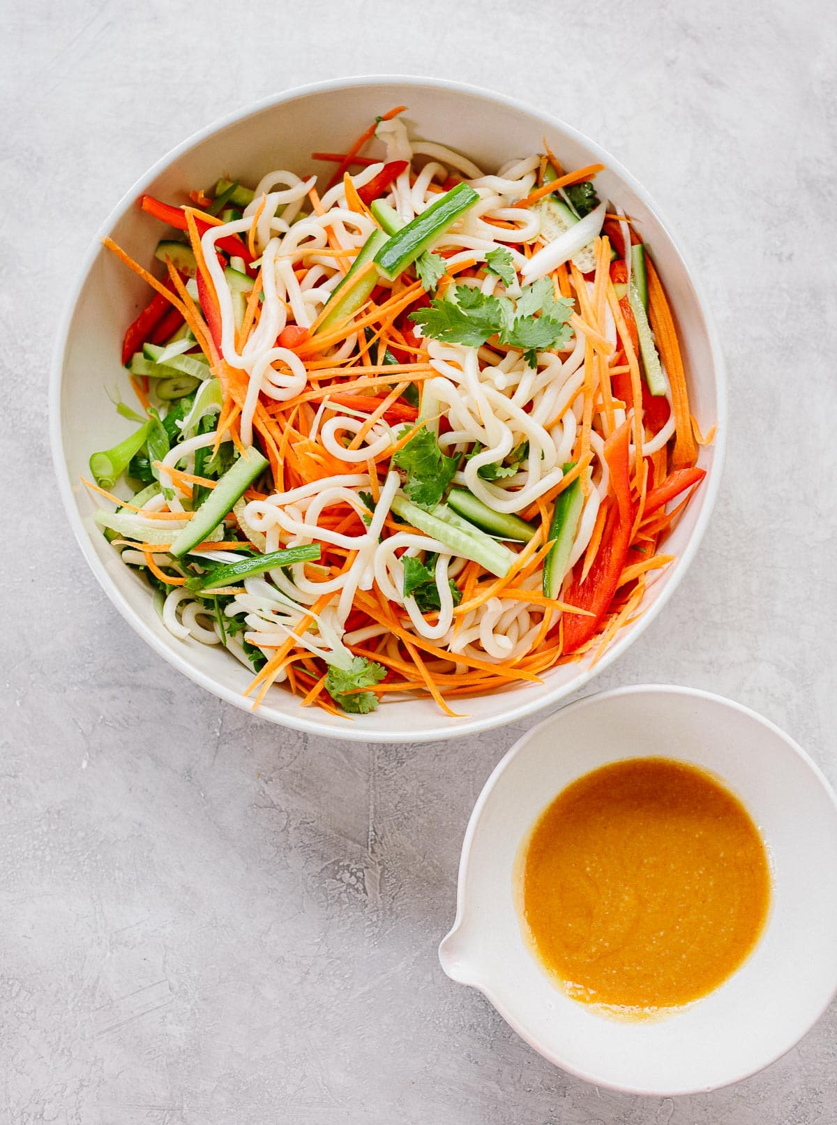 Asian noodle bowl ingredients in a bowl: White udon noodles, fresh cilantro, matchstick-cut carrots, red bell peppers and cucumbers.