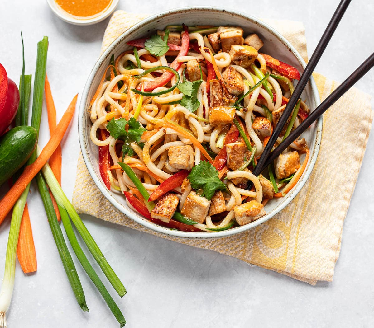 An Asian noodle bowl with chopsticks on the side, with glazed brown tofu cubes, colorful vegetables and creamy miso sauce.