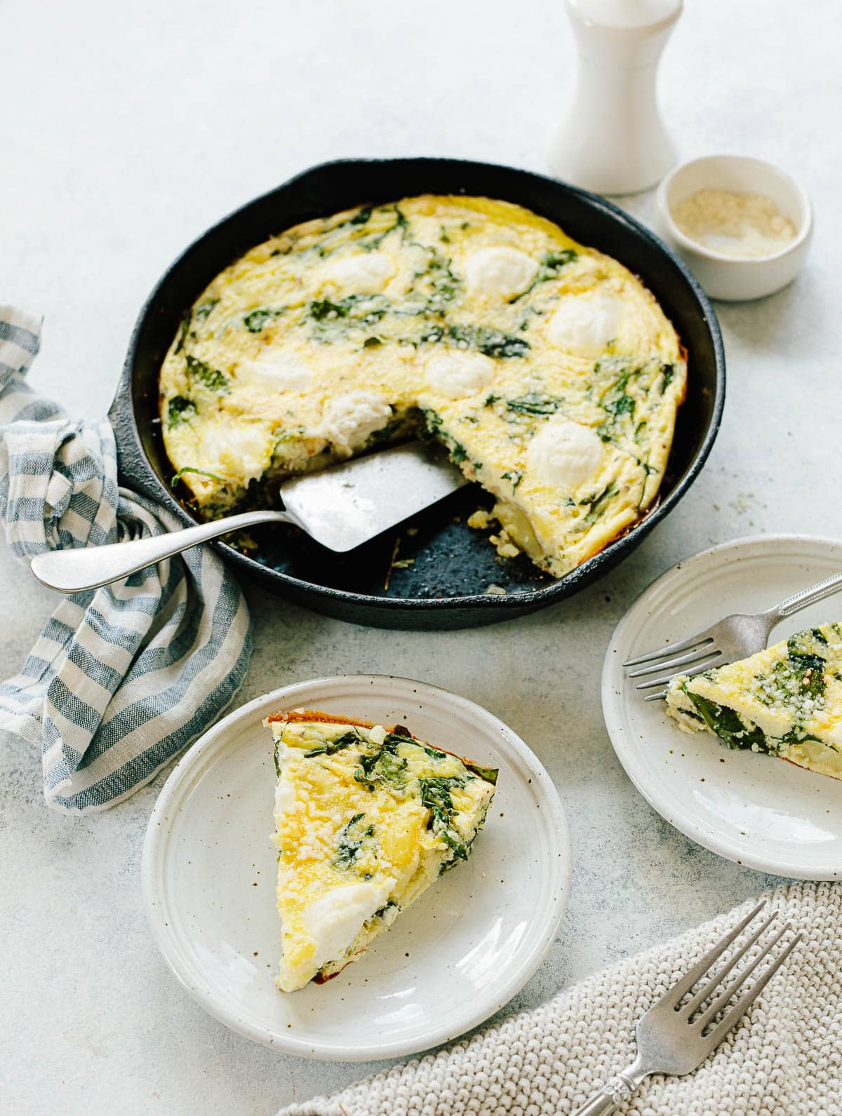 An egg and potato frittata with spinach and ricotta cheese baked in a black cast iron skillet.