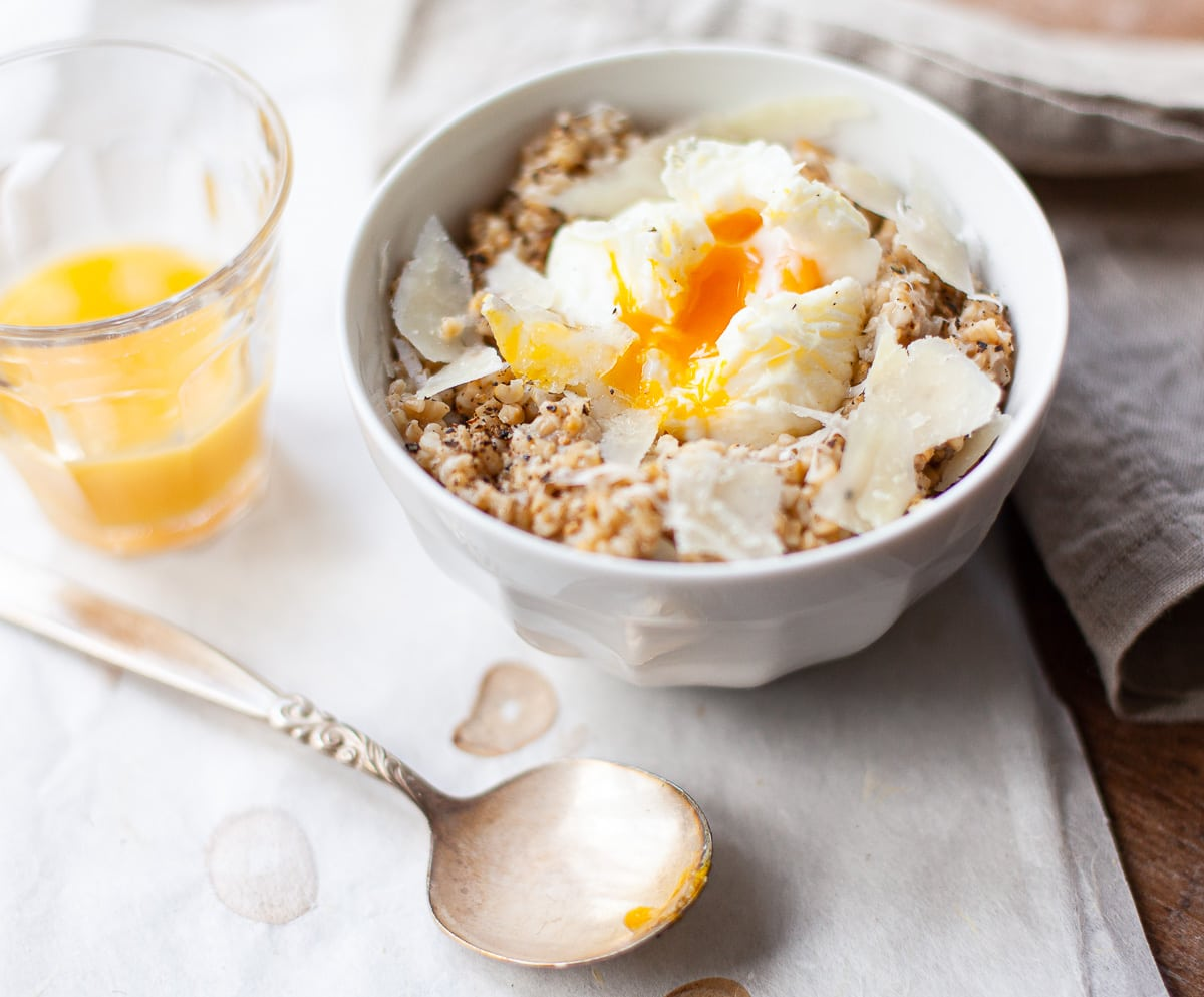 A white ceramic bowl of breakfast steel cut oats with pecorino cheese and poached egg, with a spoon and glass of orange juice.