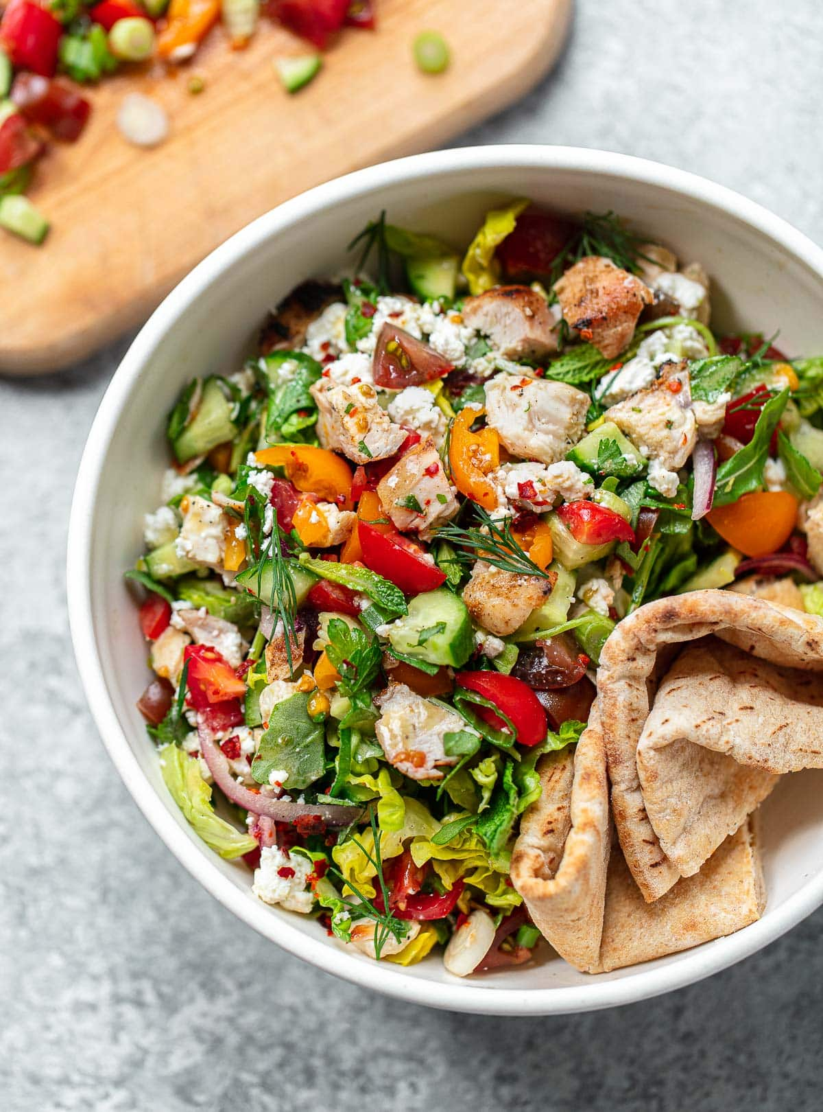 A bowl of chopped chicken salad with cucumbers and vegetables.