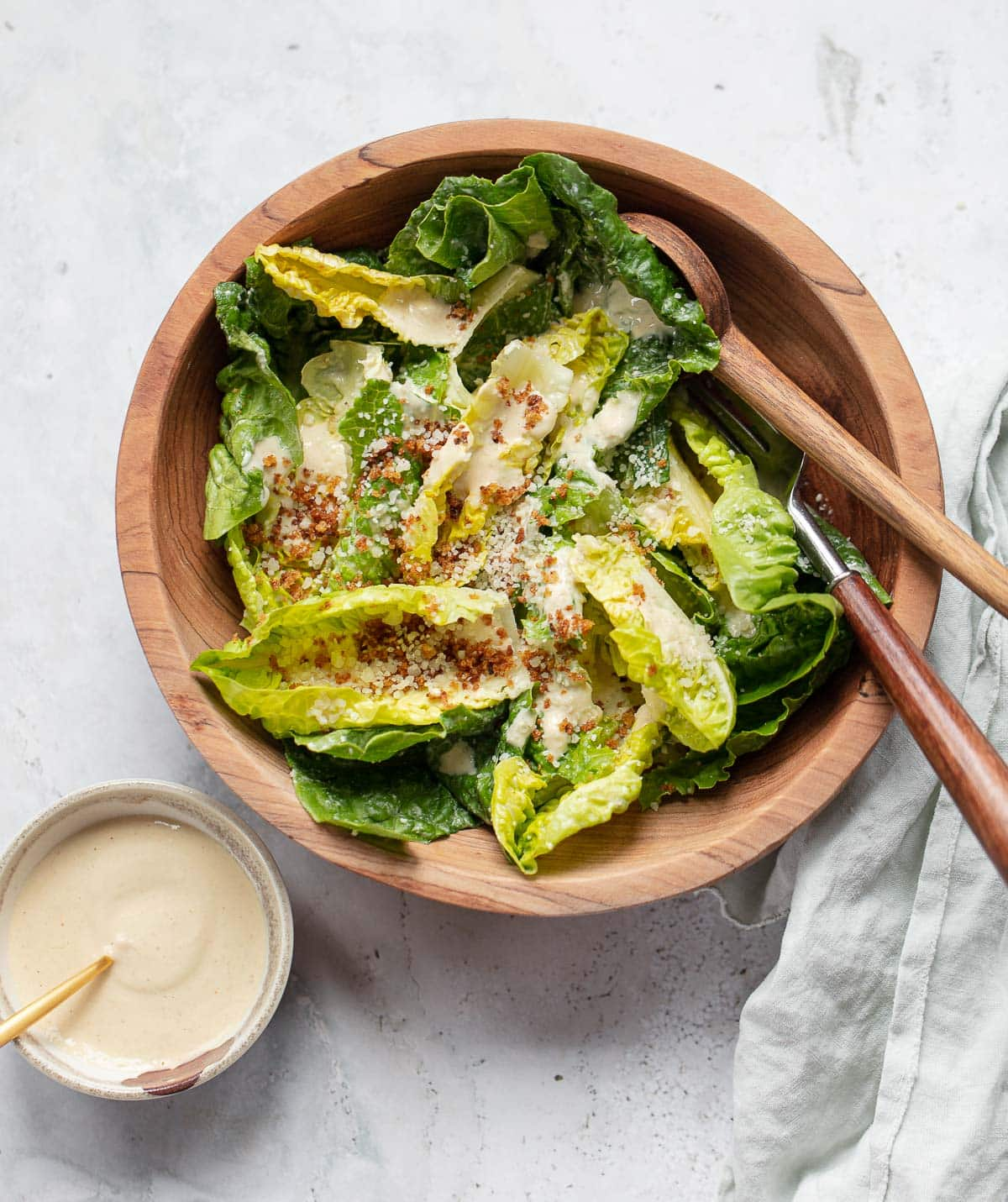 Romaine lettuce leaves in a wooden salad bowl with creamy tahini Caesar salad dressing, olive oil breadcrumbs and grated Parmesan cheese.