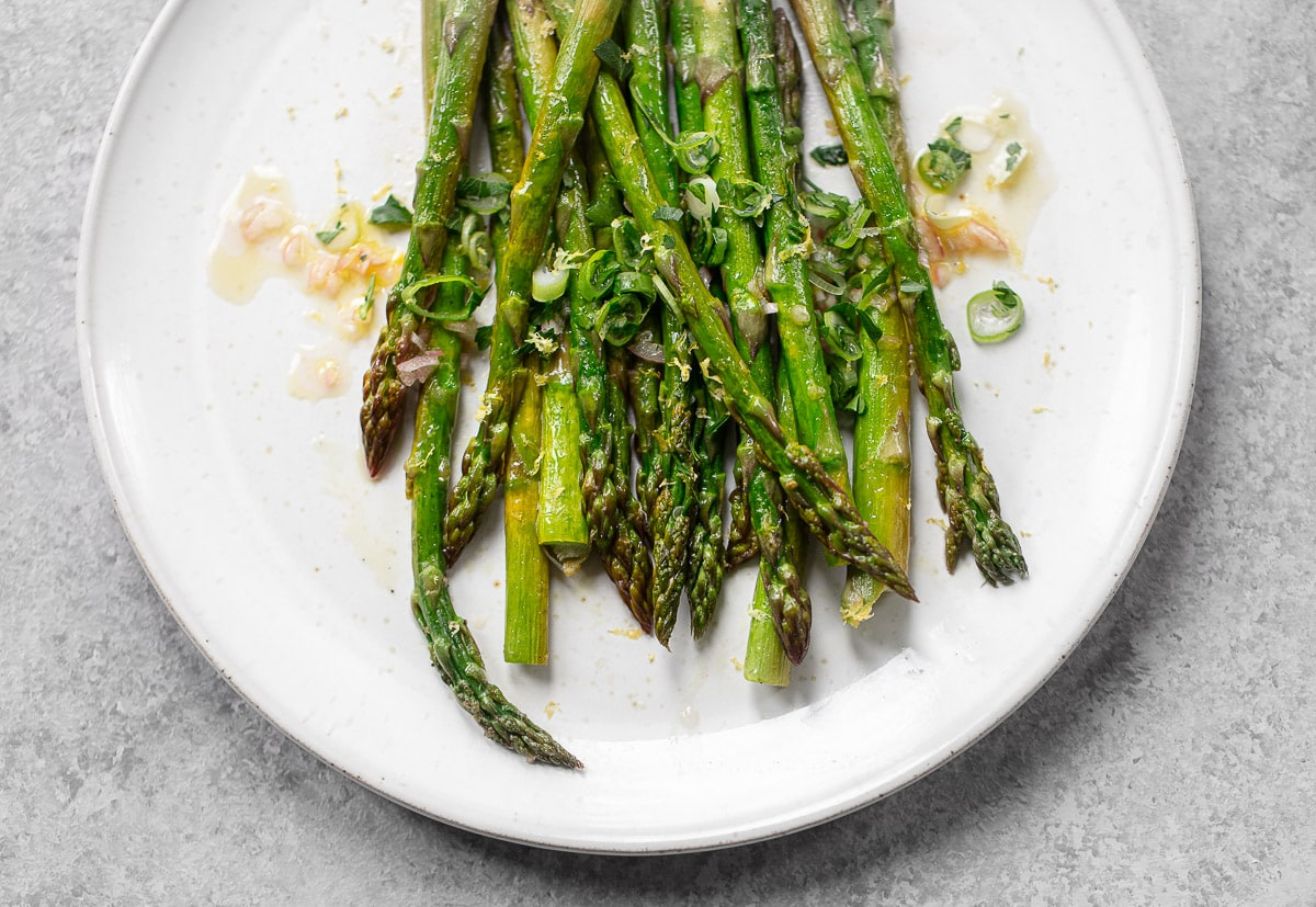 Roasted green asparagus on a white plate, drizzled with a lemon shallot vinaigrette dressing.